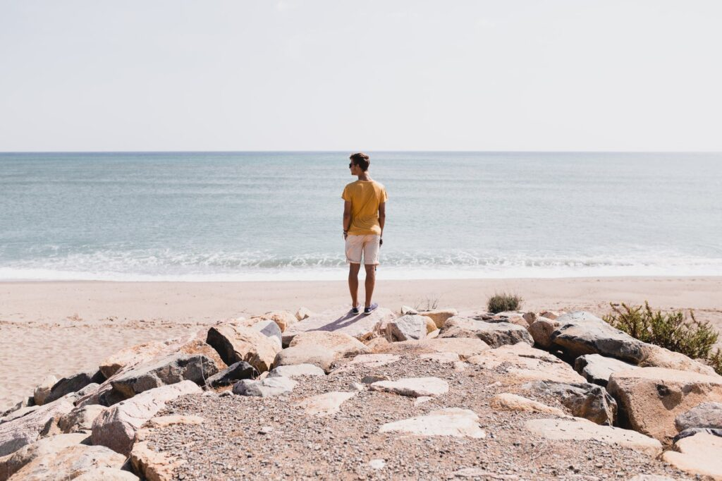 man in brown shorts standing on rocky shore